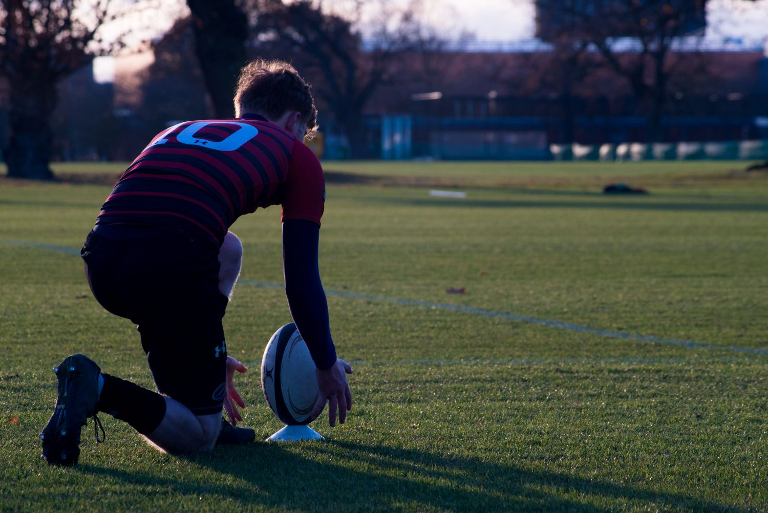 A rugby player kneels on a green pitch, reaching for a rugby ball.