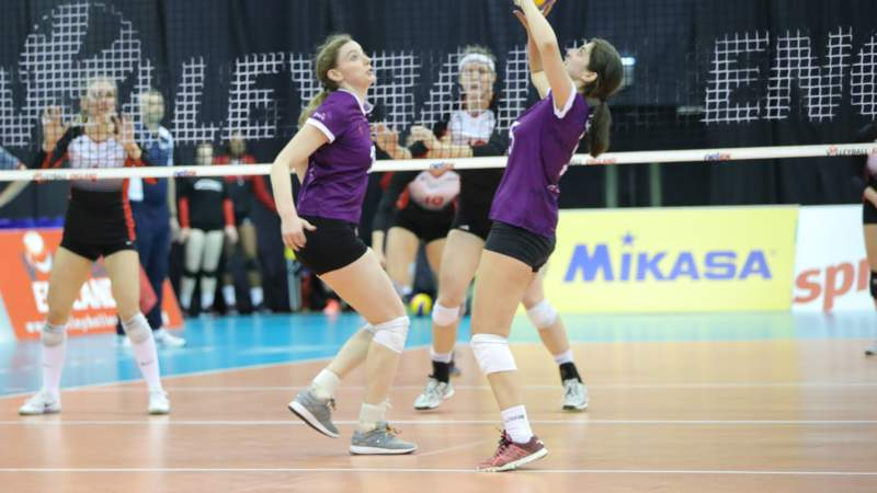 Two volleyball players wearing purple shirts jump to reach the ball, with a volleyball net and opposing team in the background.